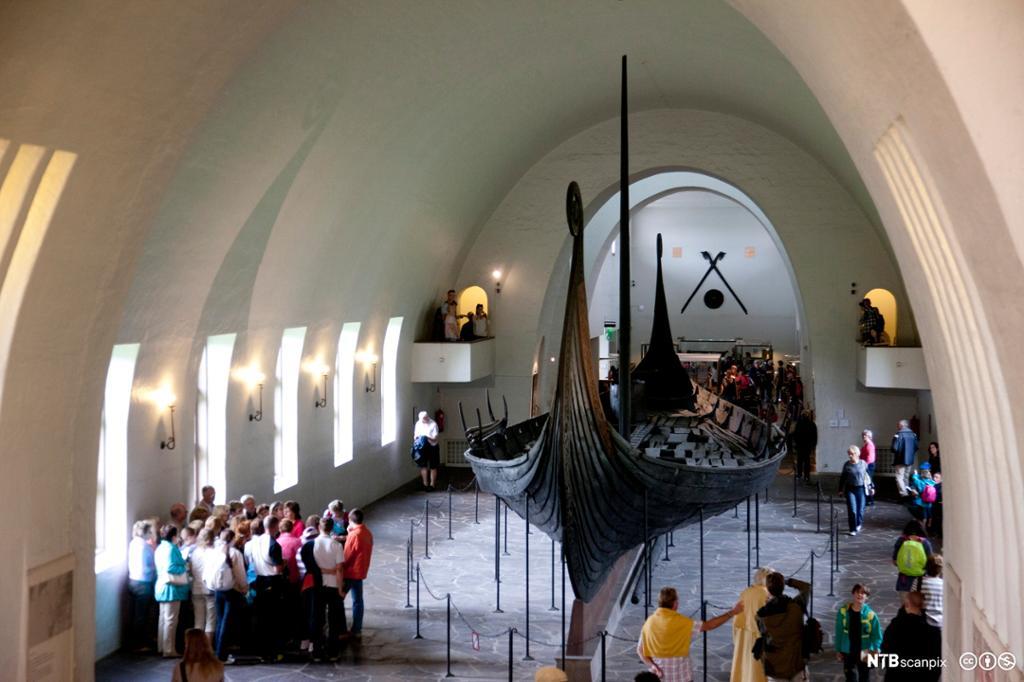 Turister ser på Osebergskipet i samlingen til Vikingskipshuset på Bygdøy i Oslo. Foto.
