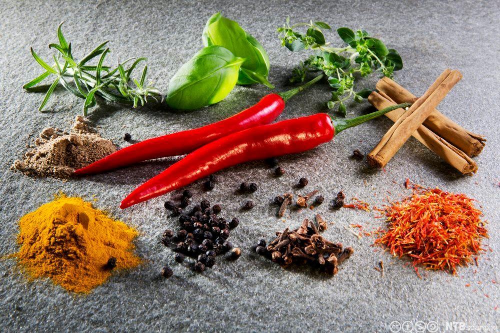 Ulike typer krydder lagt opp på en benk. Foto.