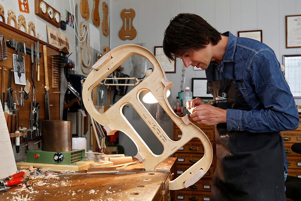 Mann lager cello i tre. Foto.
