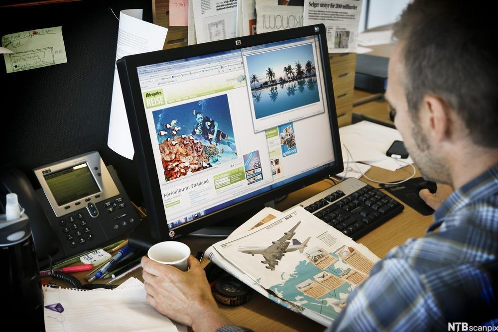 En mann ser på en dataskjerm. Foto.