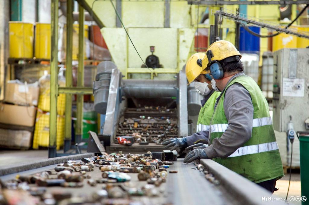 To menn sorterer brukte batterier ved et samlebånd. Foto.