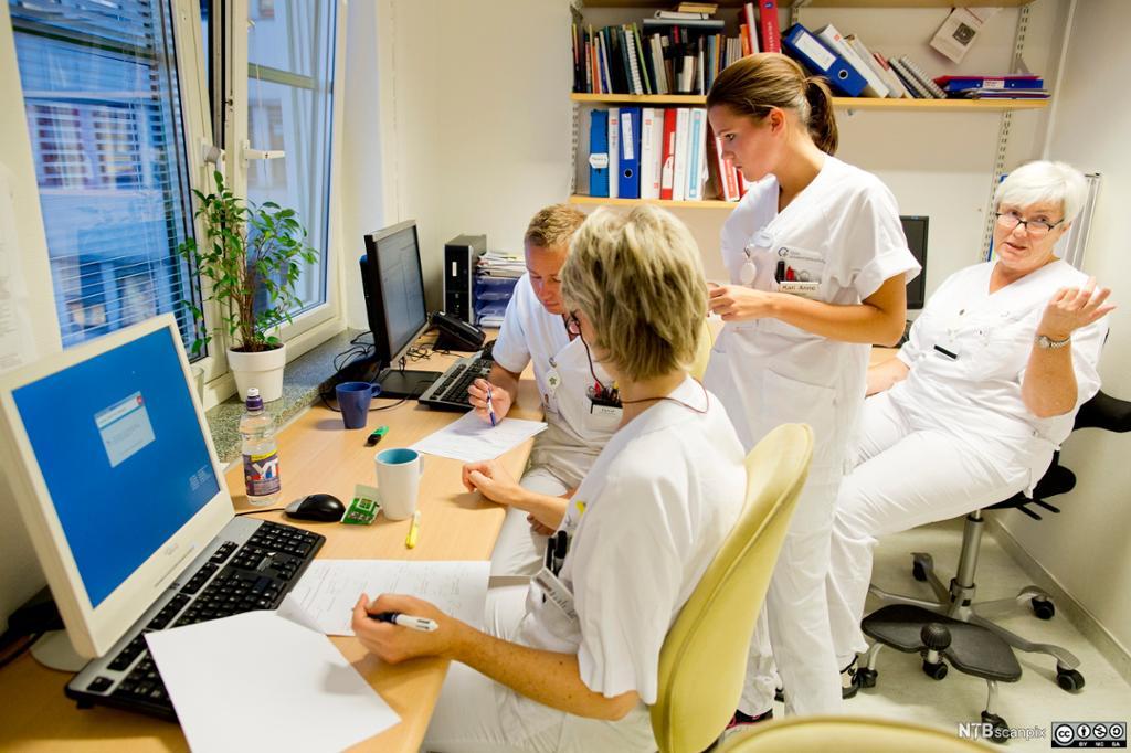Helsearbeidere på vaktrom. Foto.