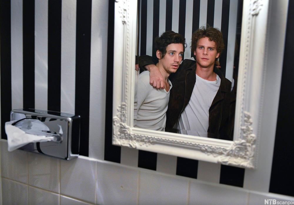 Innrammet bilde av hovedrolleinnehaverne i TV-serien Tørk aldri tårer uten hansker på et  toalett.