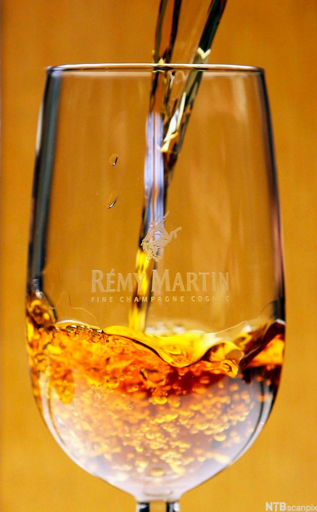 Bilete av skjenking av konjakk i eit glas. Foto.