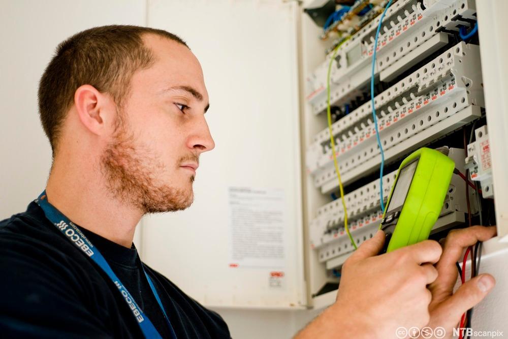 Elektriker sjekker det elektriske systemet. Foto.
