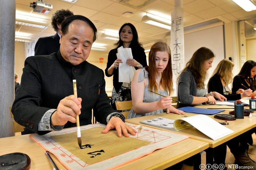 Kinesisk mann lærer studenter og skrive kinesiske tegn. Foto.
