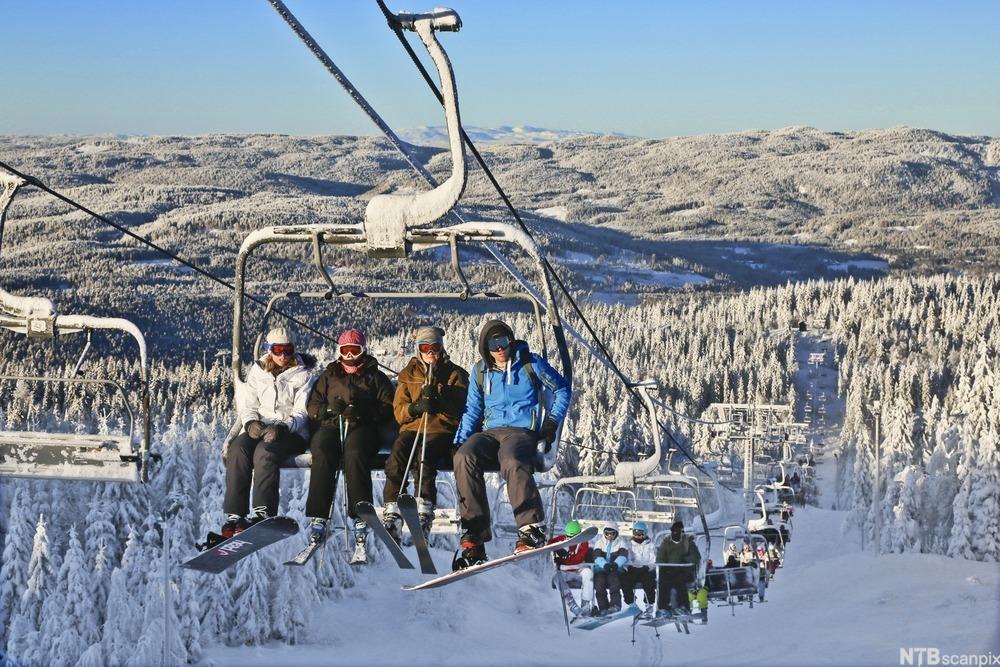 Oversiktsbilde av mennesker som sitter i stolheis med alpinski på beina. Foto.