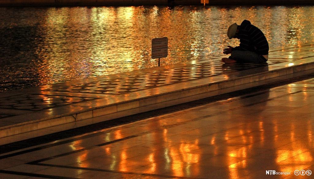 En mann mediterer ved vannkanten i nattemørkret. Foto.