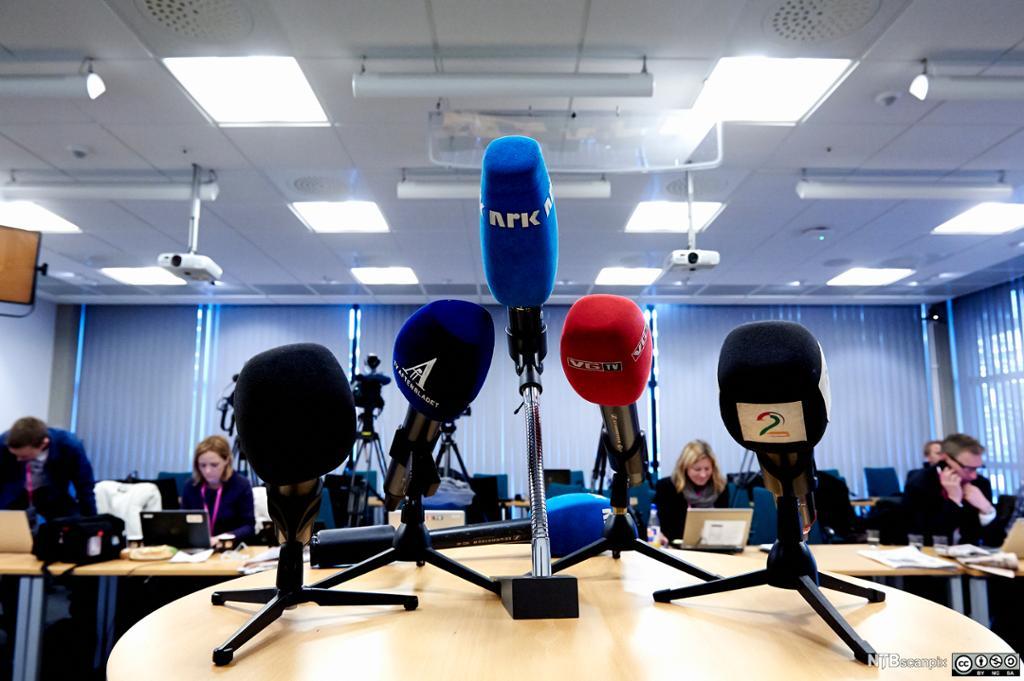 Bord med mikrofoner fra ulike TV-selskaper. Foto.
