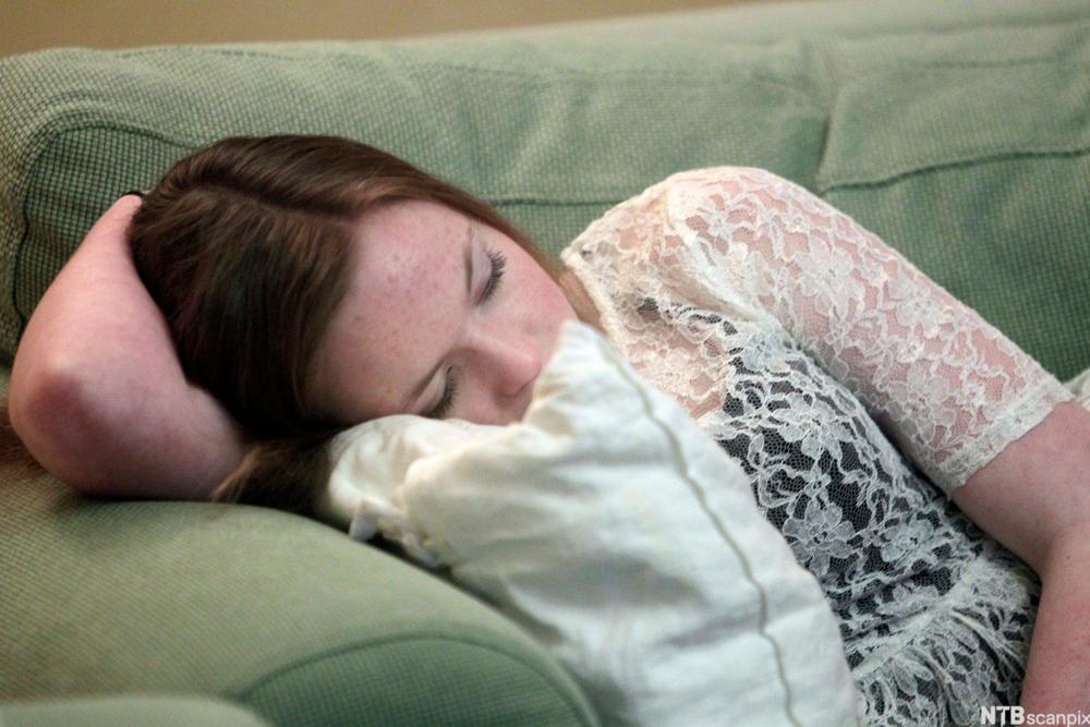 Ung jente sover på en sofa.