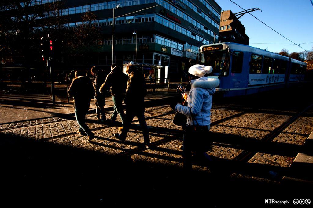 Mennesker i ferd med å krysse en fotgjengerovergang i Stortingsgata ved Nasjonalteateret i Oslo sentrum på rødt lys. En trikk venter på at fotgjengerne krysser gata. Foto.