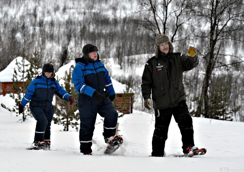 Tre personer går på truger i snøen. Foto.