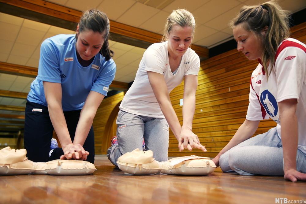 Tre personer øver på hjertekompresjoner på øvingsdokke. Foto.