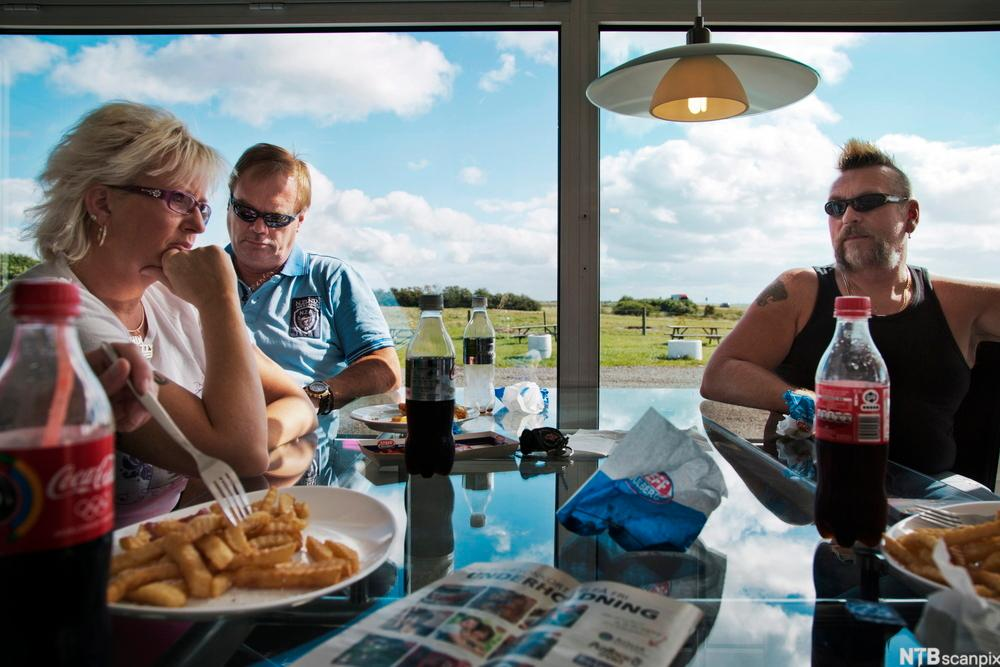 Tre voksne sitter på en cafe. Foto.