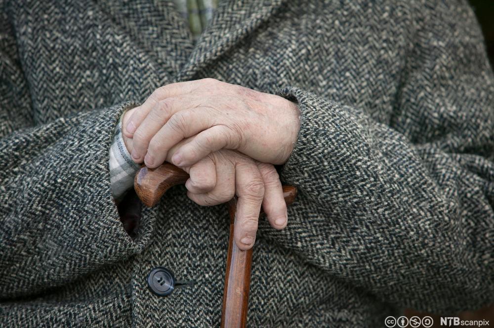 Eldre mann med stokk. Foto.