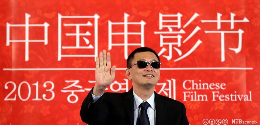 Regissør Wong Kar-wai vinker til publikum fra den røde løperen på en filmfestival. Foto.