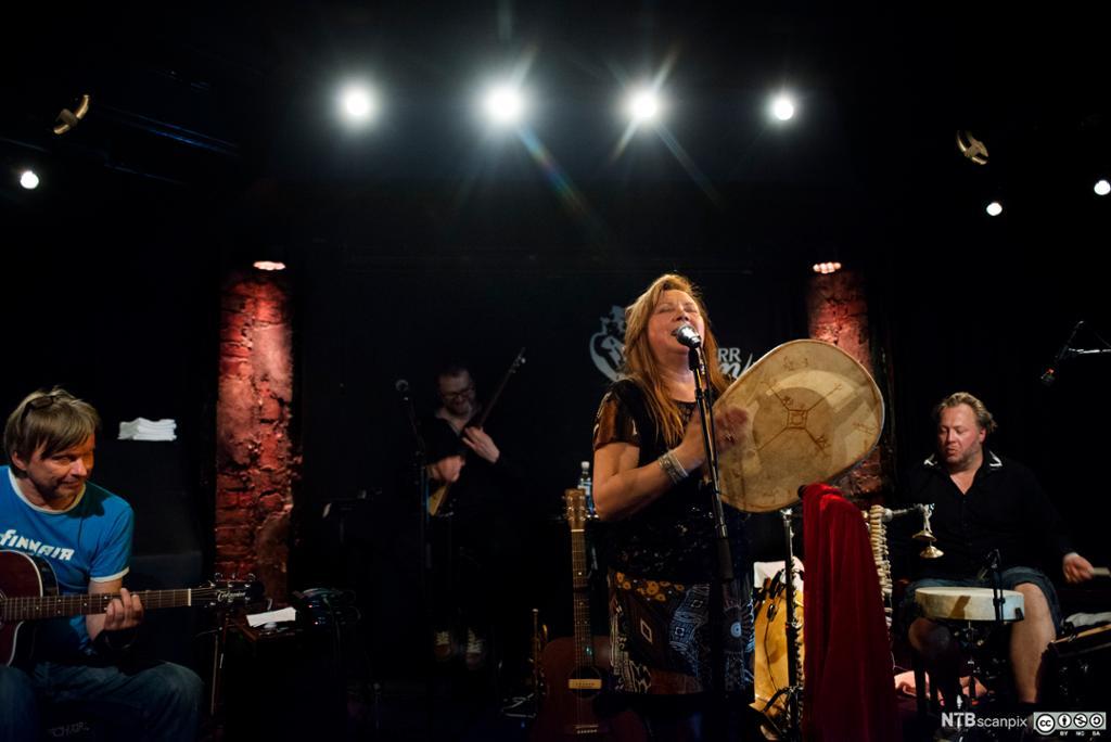 Marie Boine med runebomme på scenen sammen med bandet sitt. Foto.