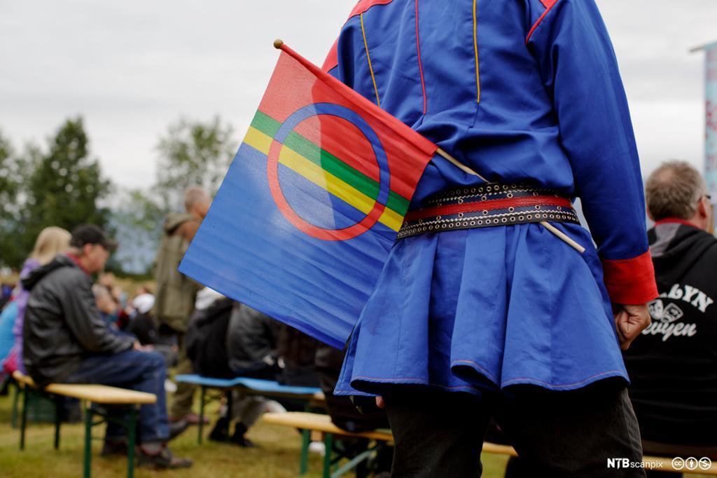 En mann i samisk kofte med samisk flagg.