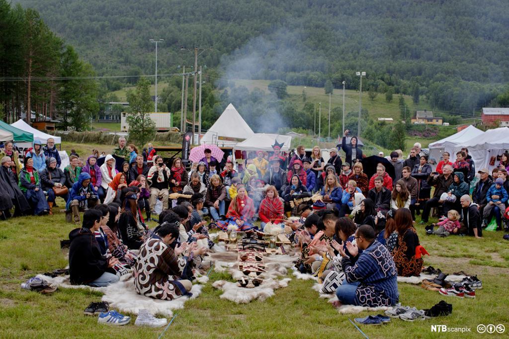 Ainu-folk og samer er kledd i nasjonaldrakter og sitter midt i en folkemengde på festivalområdet under Riddu Riddu-festivalen i 2013. Foto.