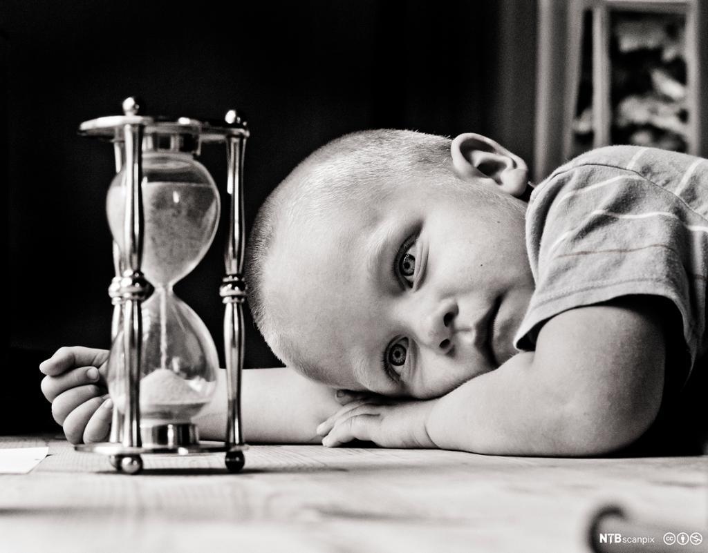 En liten gutt ligger og ser på et timeglass. Foto.