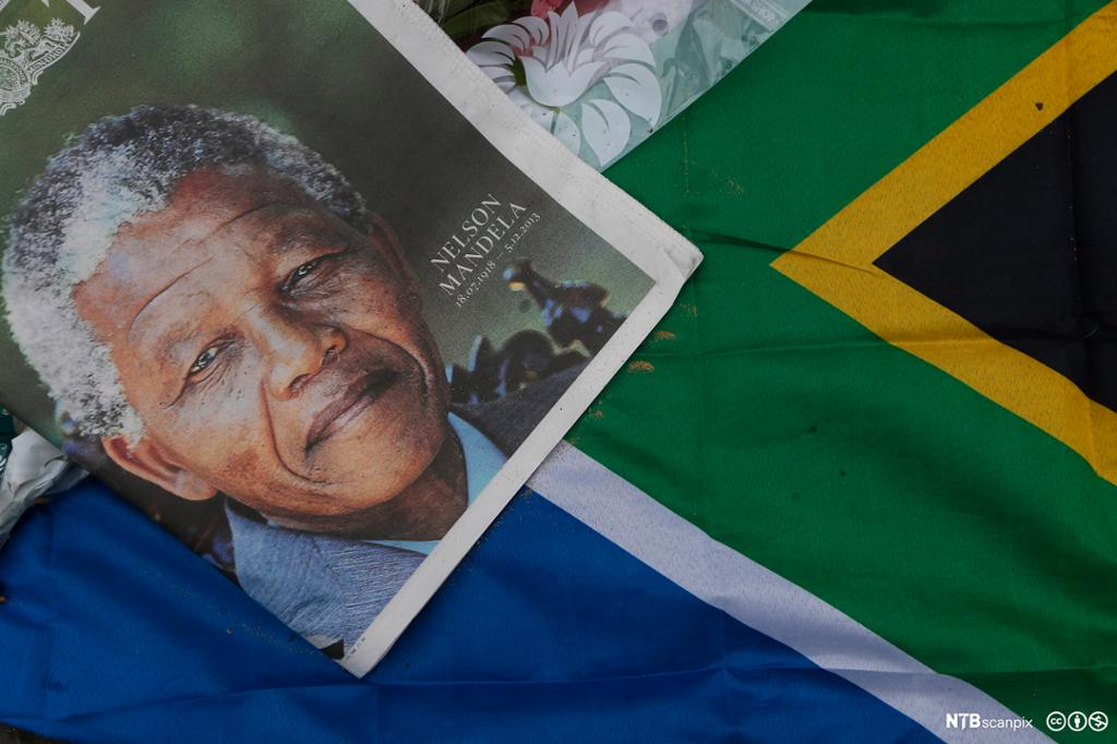 A newspaper front page picture and a South Africa flag are left in tribute for Nelson Mandela