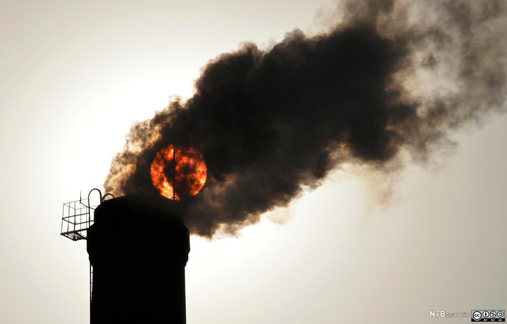 Røyk fra skorstein med sola i bakgrunnen. Foto.