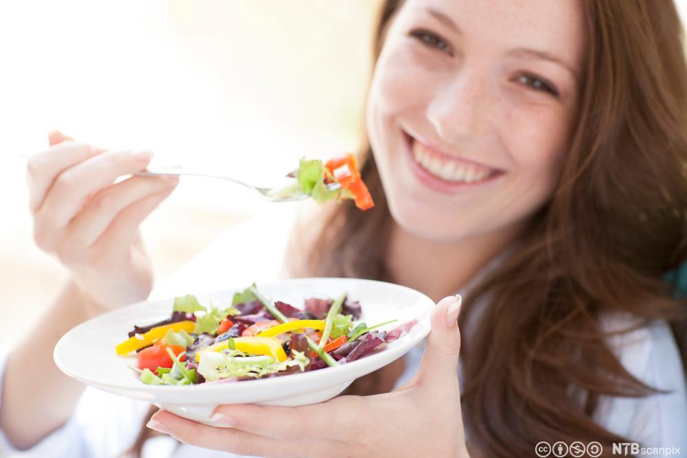 Ung kvinne spiser salat. Foto.