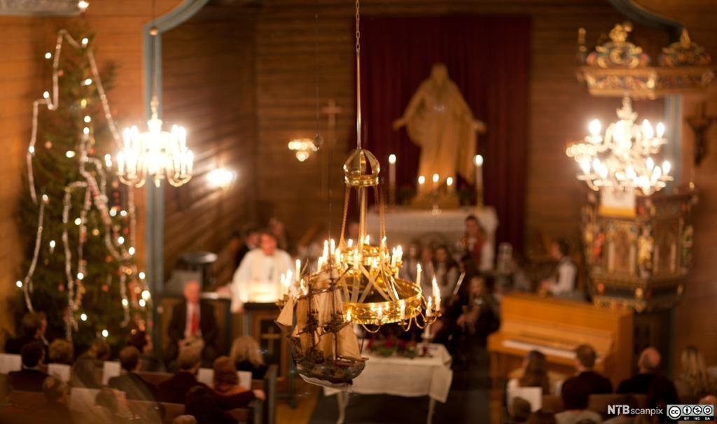 En norsk kirke på julaften pyntet med juletre og lys. Foto.