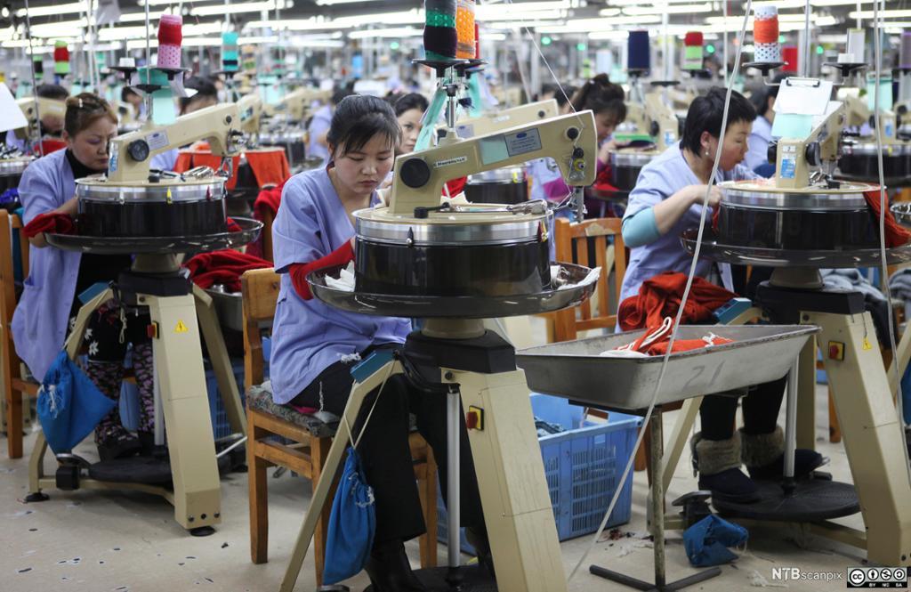 Bilde av kvinner som syr klær på en fabrikk.