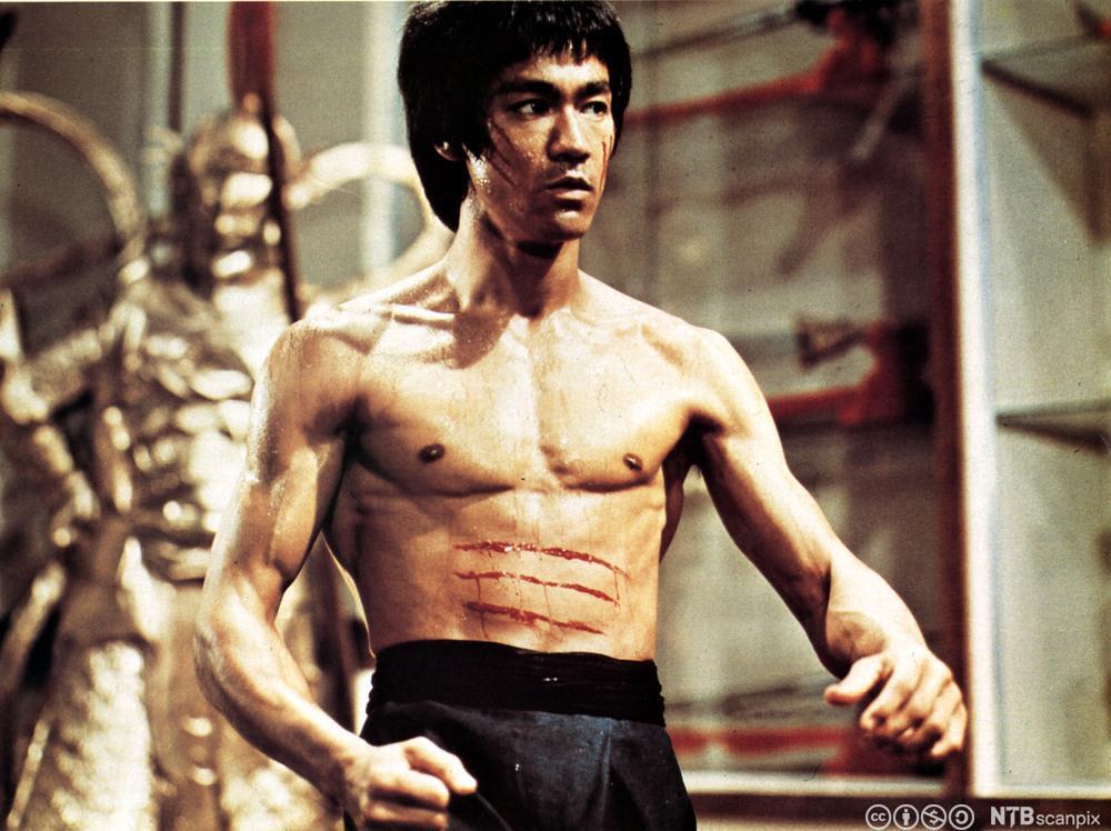 Skuespiller Bruce Lee i bar overkropp med tre blodstiper over magen fra filmen Enter the Dragon. Foto.