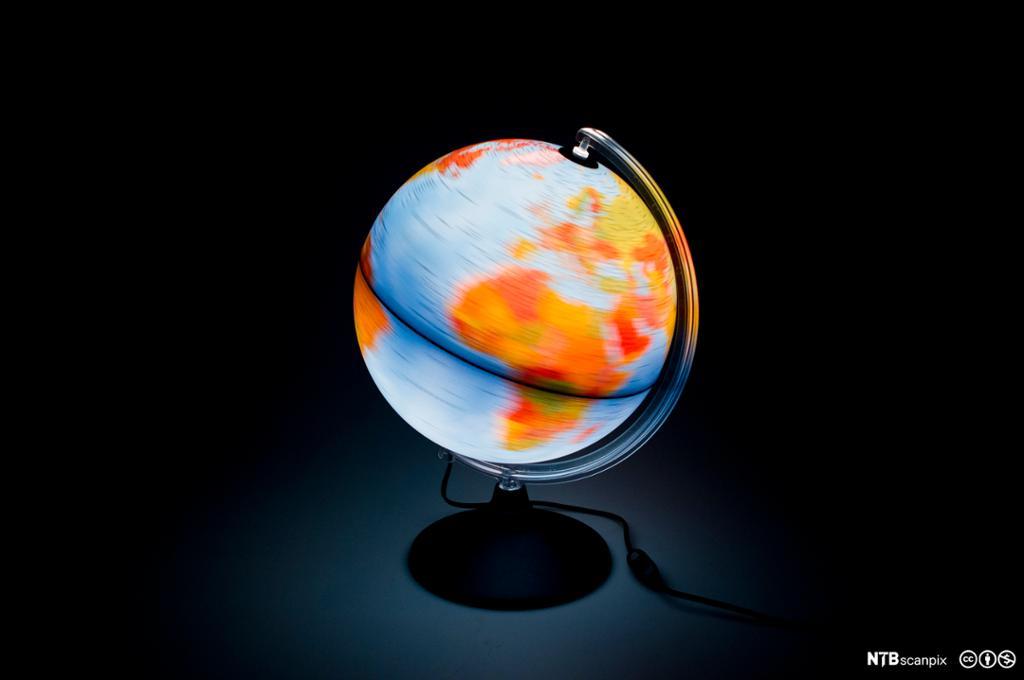 Globus snurrer rundt mot svart bakgrunn. Foto.