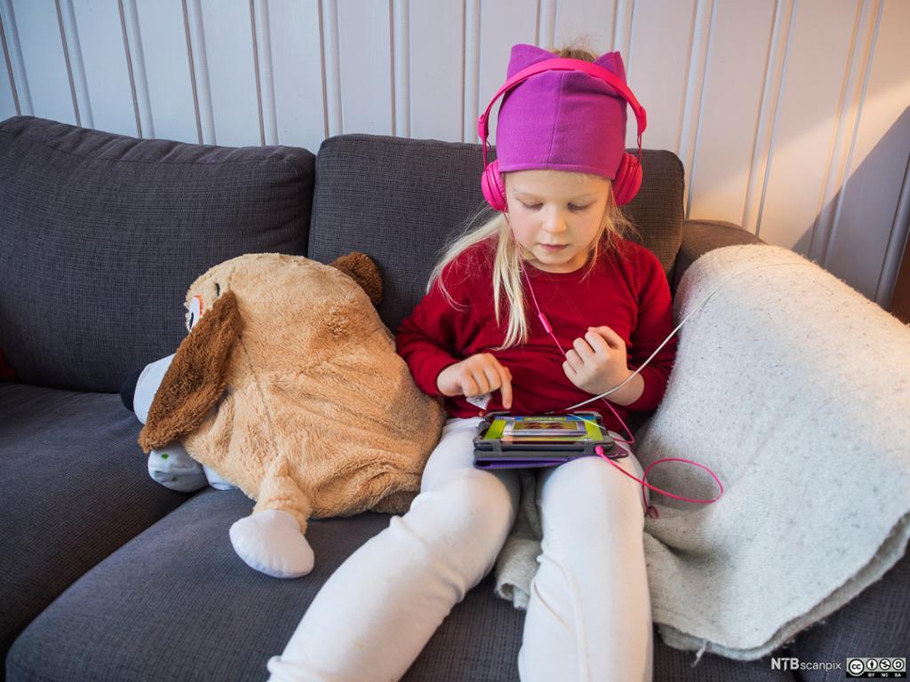 Jente med rosa headsett og Ipad. Foto.
