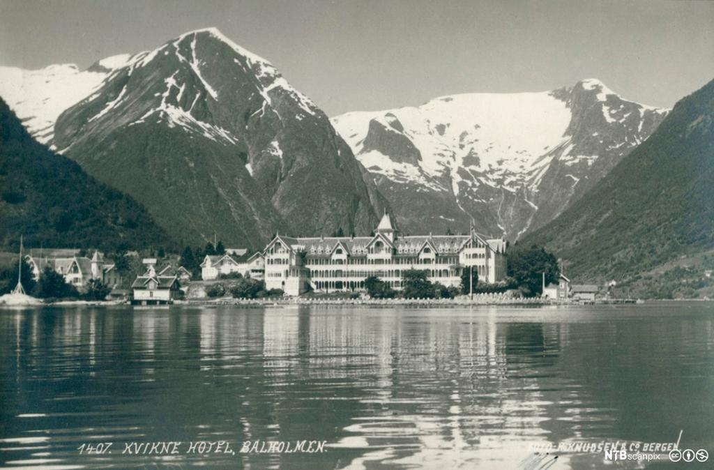 Utsikt over en fjord mot Kvikne Hotell, Balestrand med fjell som stiger opp bak. Foto.