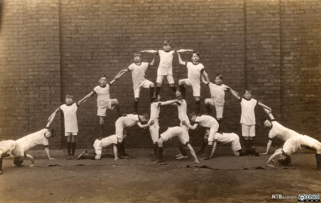 Historisk bilde av gutter som lager en menneskelig pyramide.