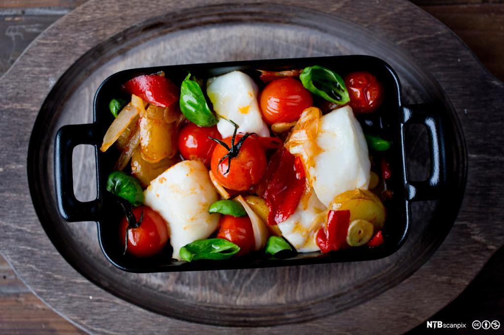 Bilete av torsk med potet, oliven og tomat. Foto.