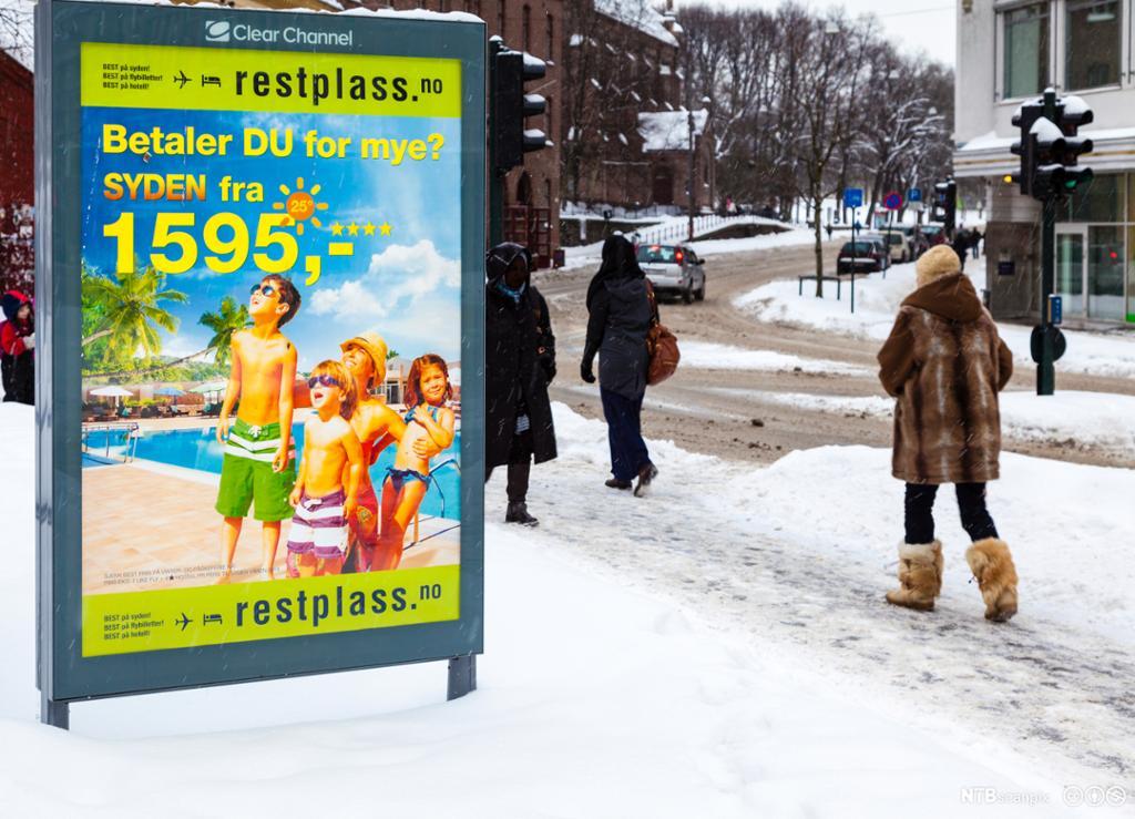 Reklameplakat for sydenreiser på snørikt fortau. Foto.