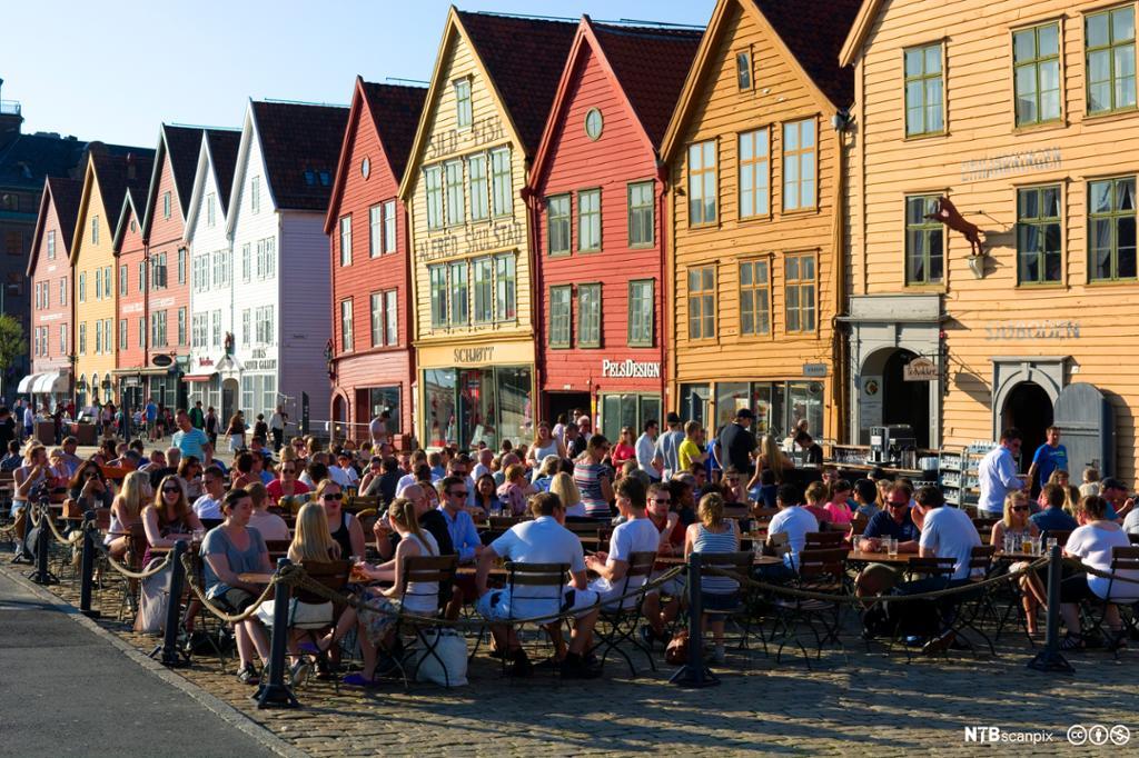 Folk hygger seg på uterestaurant på Bryggen i Bergen. Foto.