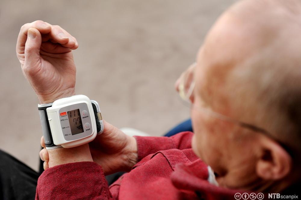 Eldre mann med blodtrykksmåler. Foto.