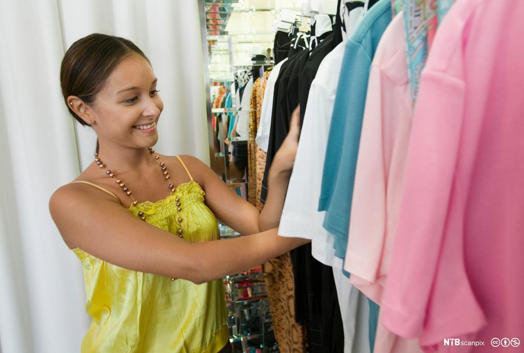 Kvinne i klesbutikk. Foto.