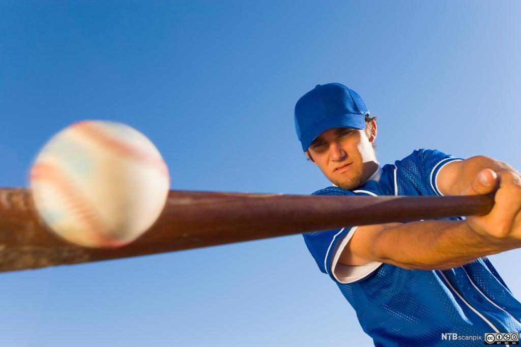 Mann som slår baseball med balltre. Foto.