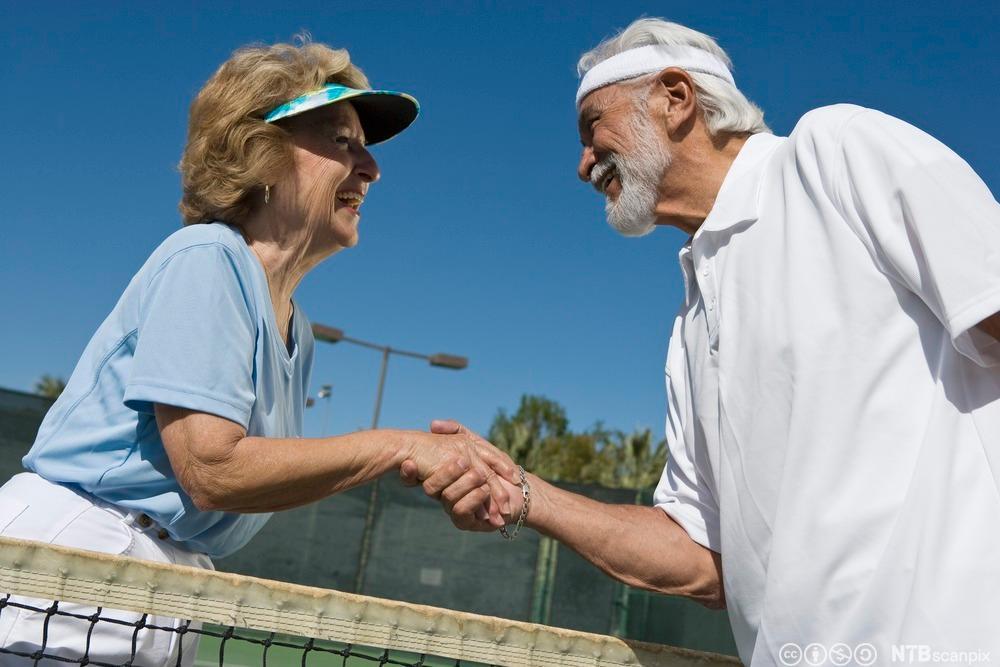 Eldre par som håndhilser over et tennisnett. Foto.