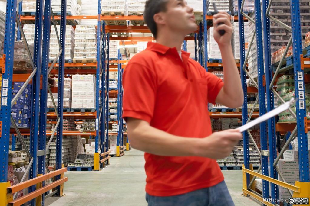 Arbedier i et stort lagervarehus snakker i walkie-talkie. Foto.