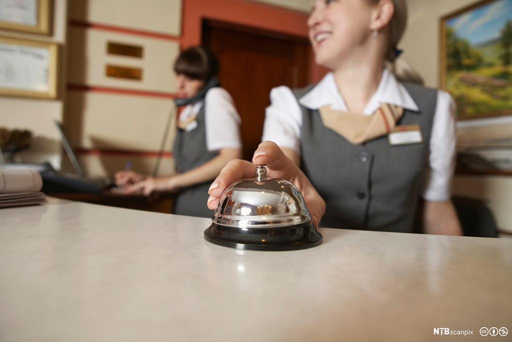 Smilende kvinnelig resepsjonist på hotell.