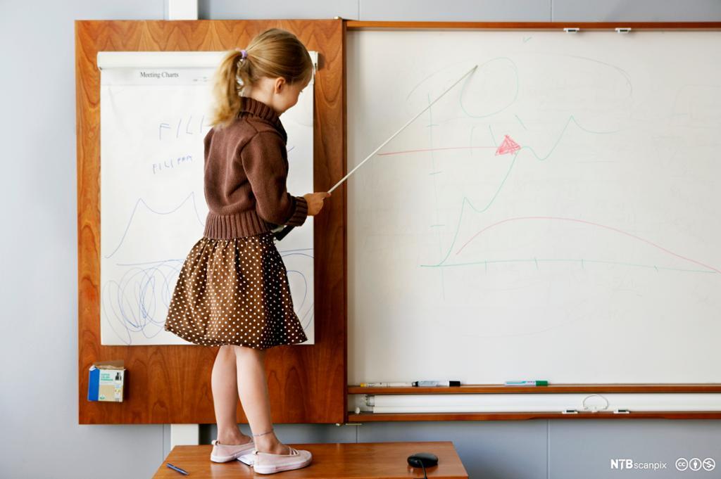 Jente tegner på en tavle i et klasserom. Foto.