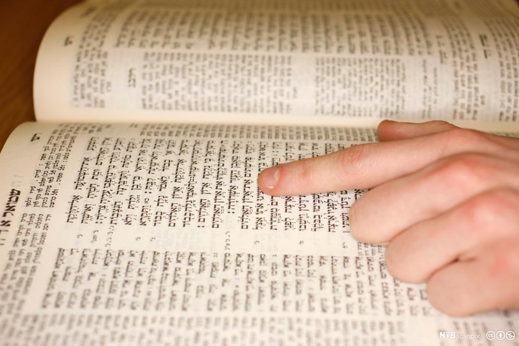 Oppslått bok med hebraisk skrift. Sidene er inndelt i ulike kolonner og tekstbokser. En hånd ligger på boken. Pekefingeren følger teksten. Foto.