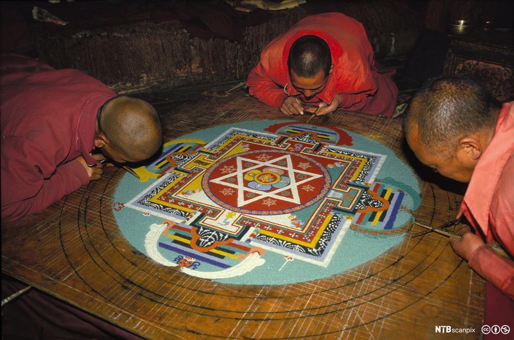 Tre munker lager kunstverk av sand i ulike farger. Foto.