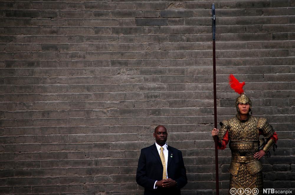 Amerikansk sikkerhetsvakt og kinesisk vakt i historisk krigerkostyme. Foto.