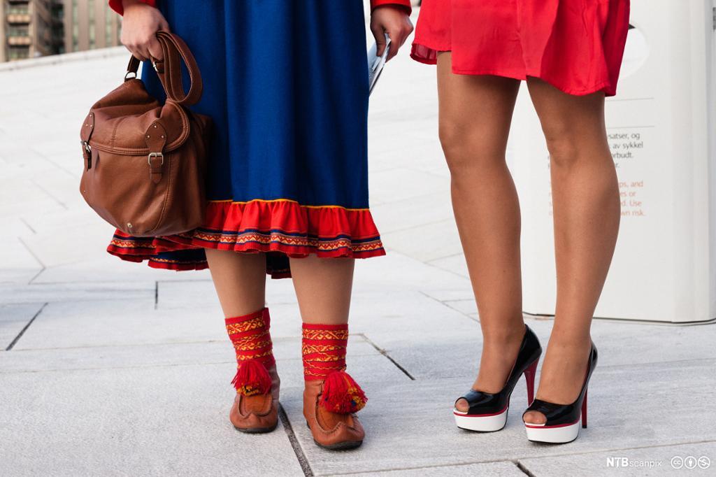 To kvinner derav én med samisk fottøy og og én med høye heler. Foto.