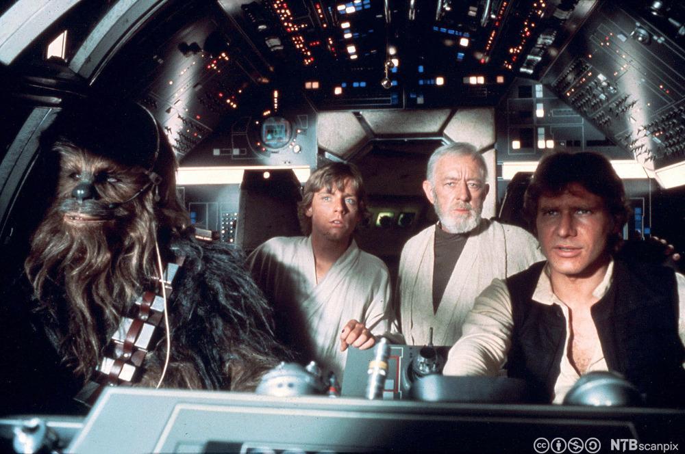 Star Wars-karakterene Chewbacca, Luke Skywalker, Obi-Wan Kenobi og Han Solo sitter i et romskip. Filmfoto.