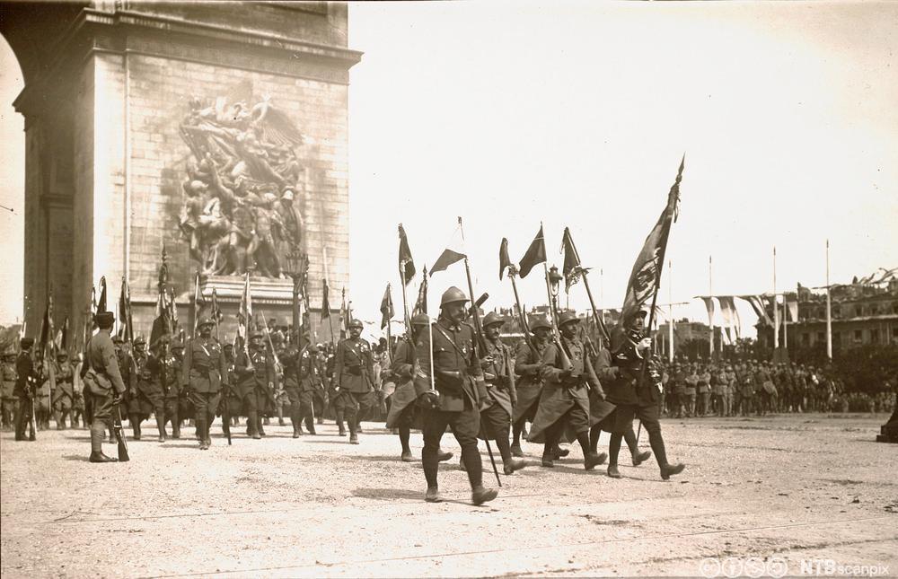 Feiring av de alliertes seier etter første verdenskrig. Tropper marsjerer under triumfbuen i Paris på den franske nasjonaldagen i 1919. Foto.